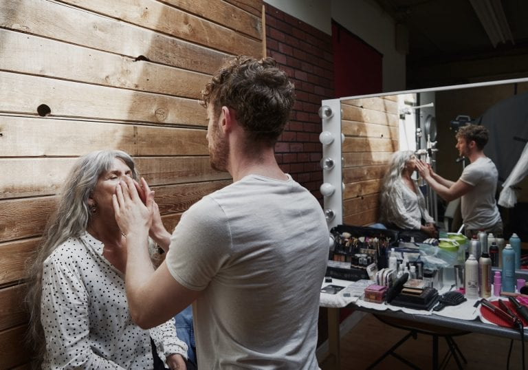 Behind the scenes image of a make up artist working with a mature model with long silver hair by Vancouver contemporary portrait photographer Angela McConnell