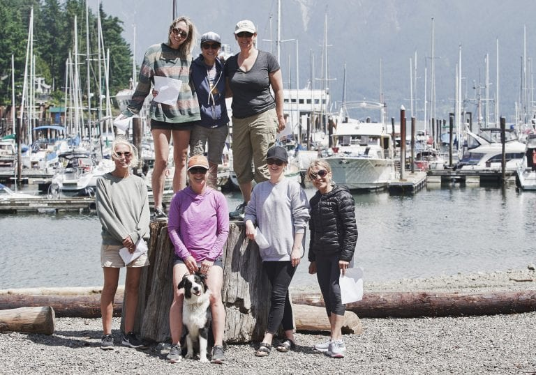 Women and an Australian shepherd pose during a group photo at Bowen Island at a courage and bravery workshop by Vancouver workshop and retreat photographer Angela McConnell