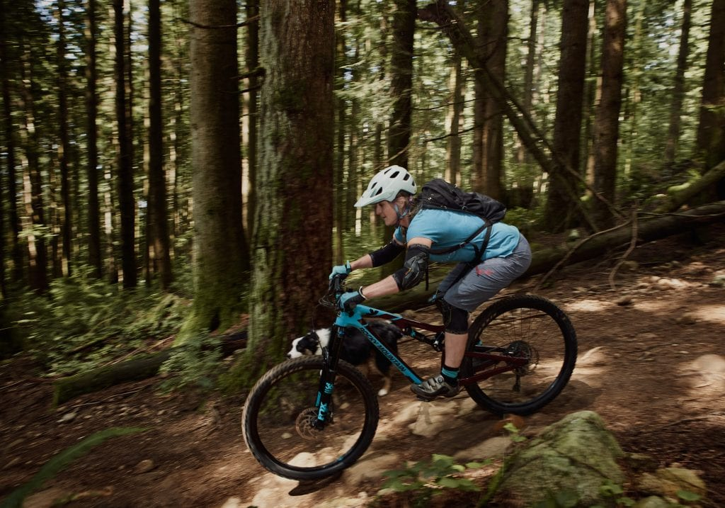 Coaching client keeping passionate in business by mountain biking with Australian shepherd at Mt Fromme by Vancouver business portrait and branding photographer Angela McConnell