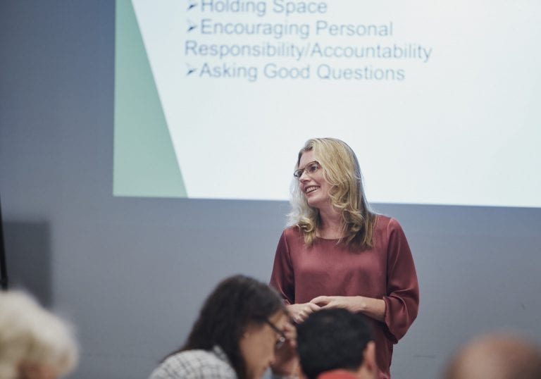 A woman smiles while presenting a keynote at a group training event by Vancouver business portrait and branding photographer Angela McConnell