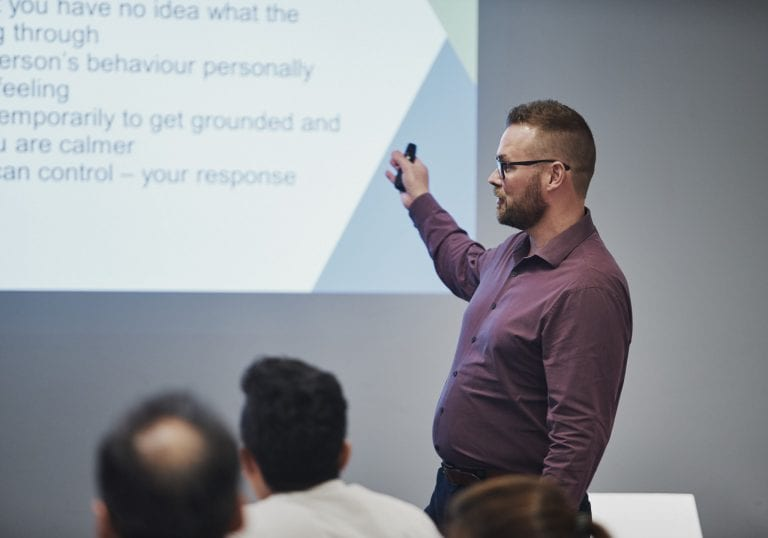 A man presents a keynote at a group training event by Vancouver business portrait and branding photographer Angela McConnell