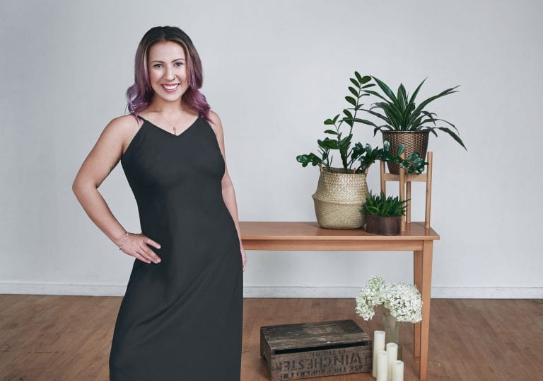 Woman in a black dress smiles at the camera for a milestone birthday portrait session by Vancouver contemporary portrait photographer Angela McConnell