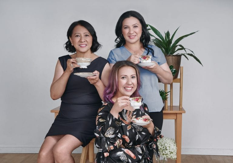 Mother and daughters smile at the camera with cups of tea for a milestone birthday portrait session by Vancouver contemporary portrait photographer Angela McConnell