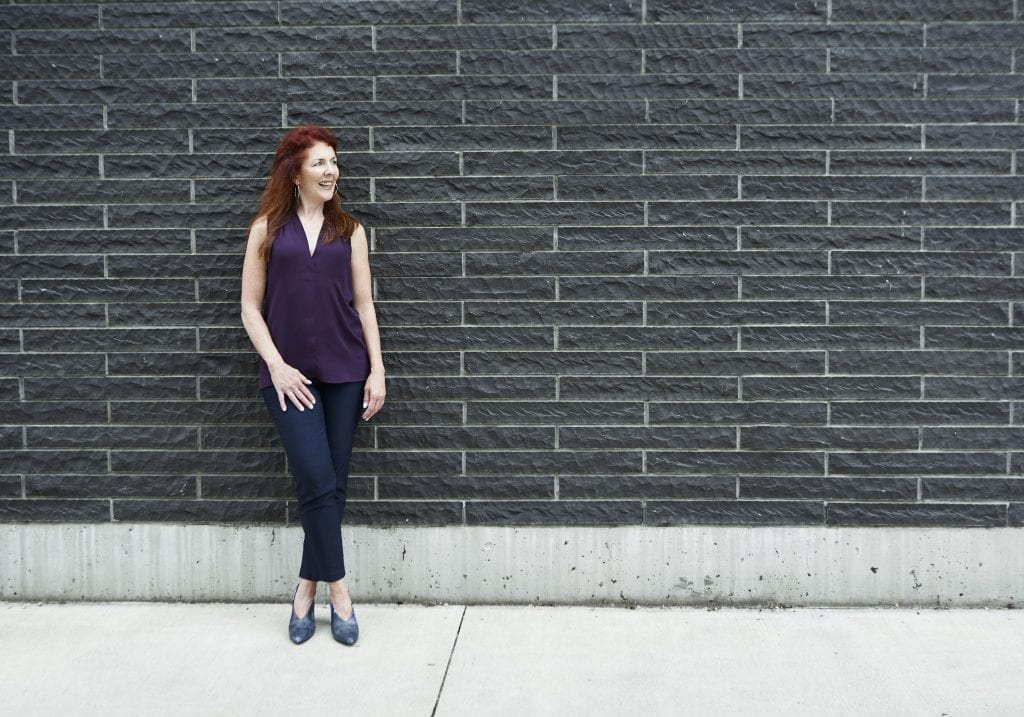 A woman with red hair leans against a grey brick wall smiling off camera during a business portrait and branding session with Vancouver photographer Angela McConnell